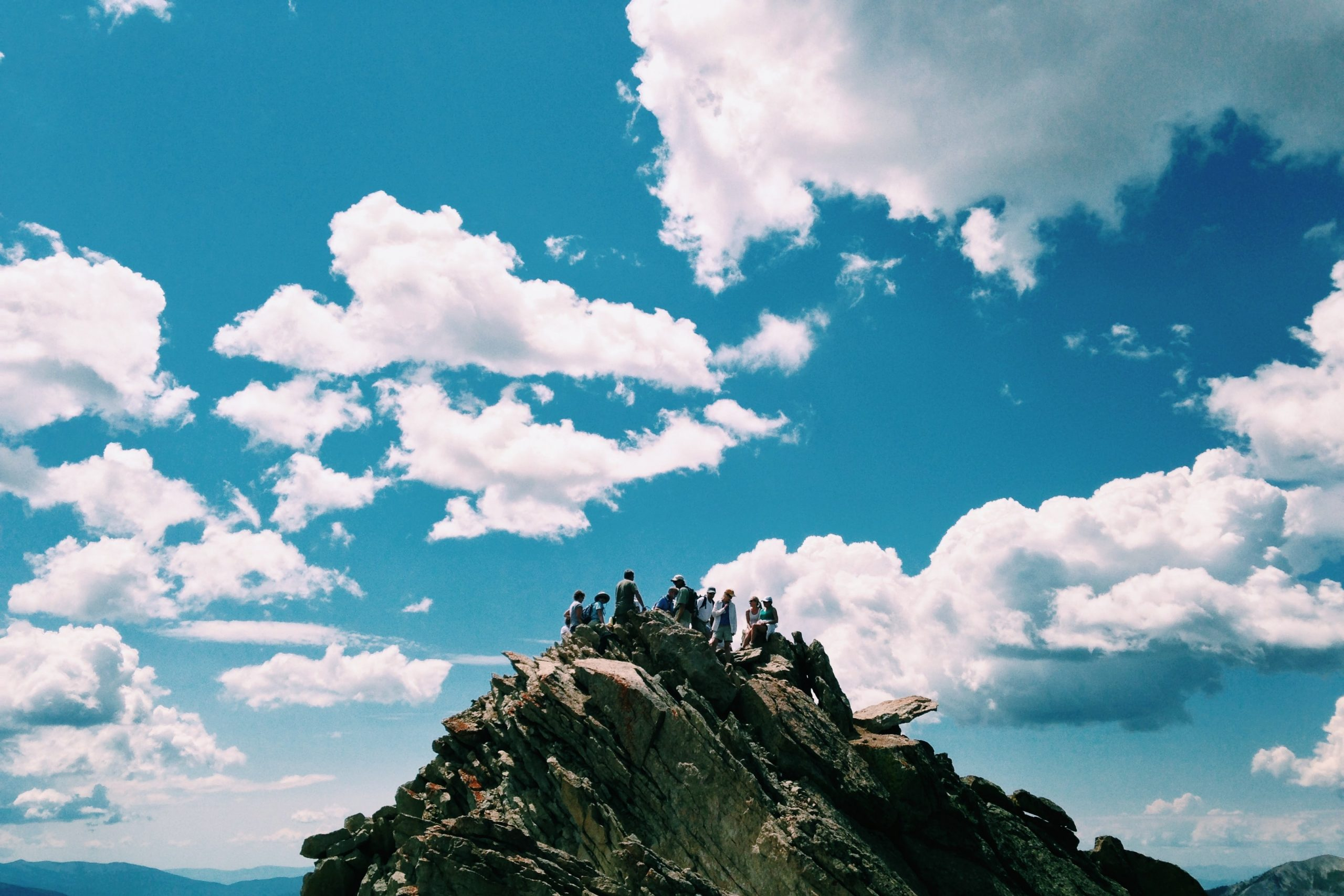 People gathering on mountain top against background of clouds